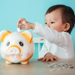 little baby moneybox putting a coin into a piggy bank - kid saving money for future concept
